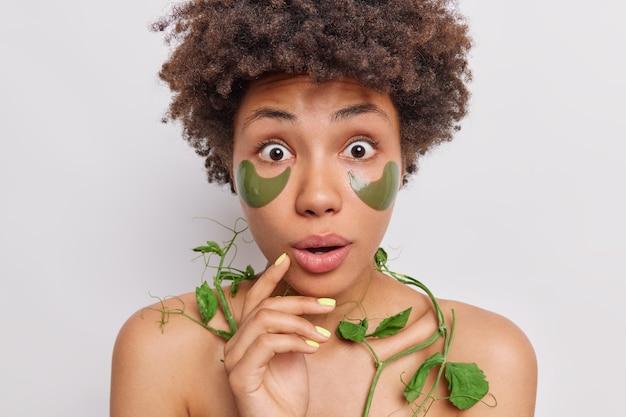 Frau starrt beeindruckt in die kamera trägt grüne hydrogel-pflaster auf verwendet grüne erbsenpflanze, die feuchtigkeitsspendende und glättende anti-aging-vorteile für haut und haar bietet