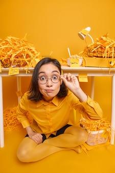Frau starrt verwundert an, kann ihren augen nicht trauen, trägt eine runde brille, stilvolle kleidung posiert im schrank im coworking space auf gelb