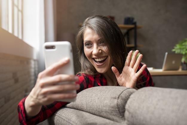Frau startet einen videoanruf mit ihrem smartphone auf dem sofa