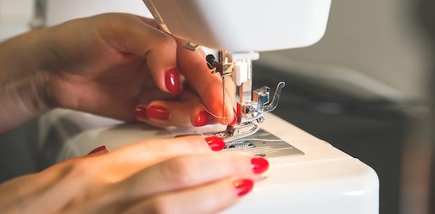 Frau steckt faden in nähmaschine. mädchenhände bei freiberuflicher arbeit. mode-konzept. erstellen von neuen kleiderprozessen. hobby-ideen.