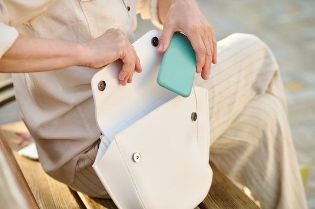 Frau steckt smartphone in weiße handtasche