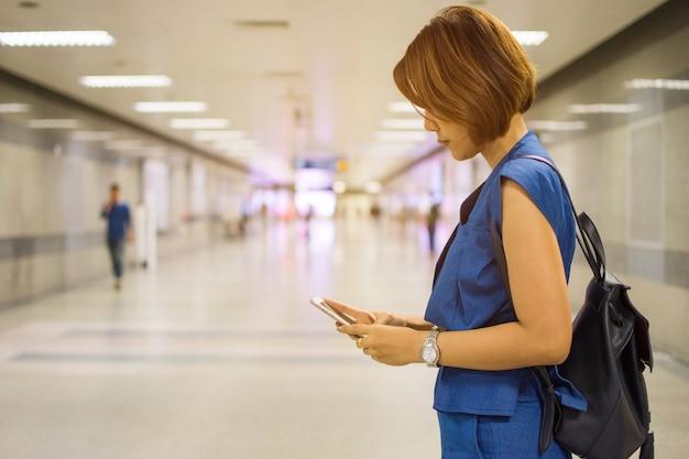 Frau stehen und berühren smartphone in der u-bahn. thema ist verschwommen und low key.