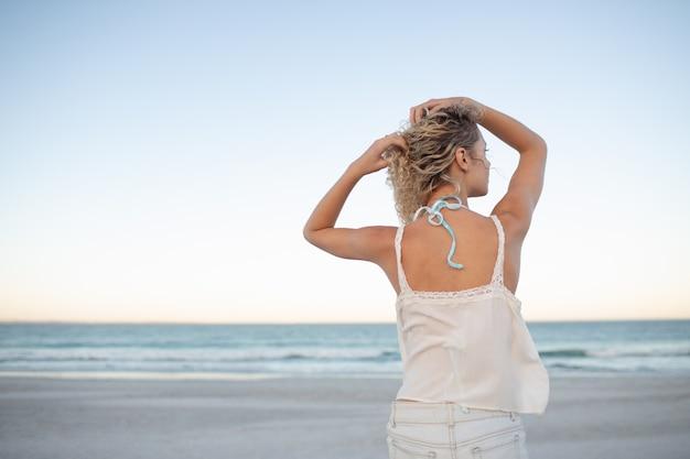 Frau stehend mit den händen im haar am strand