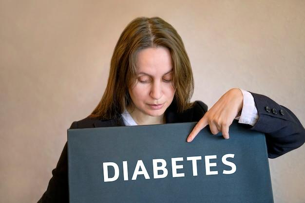 Frau steht auf und zeigt mit dem finger auf die inschrift an der tafel diabetes