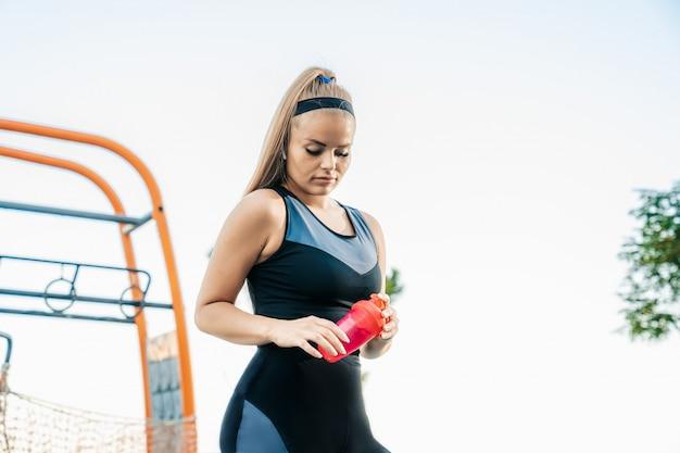 Frau steht im fitnessstudio im freien mit einer flasche wasser