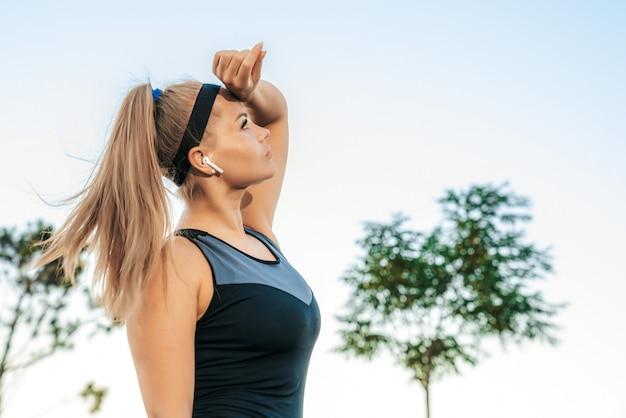 Frau steht im fitnessstudio im freien mit kopfhörern