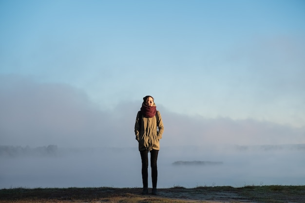 Frau steht im morgensonnenlicht vor der schönen naturlandschaft, die mit nebel bedeckt ist. weiblicher wanderer, der aufgehende sonne im nebligen natürlichen hintergrund genießt