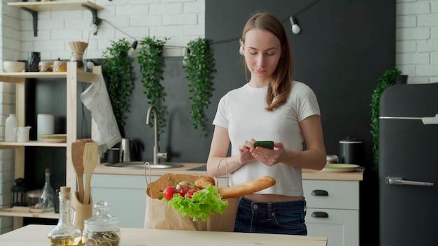 Frau steht in der küche in der nähe einer papiertüte voller frischer lebensmittel und verwendet eine smartphone-app, um sie an den supermarkt zu liefern