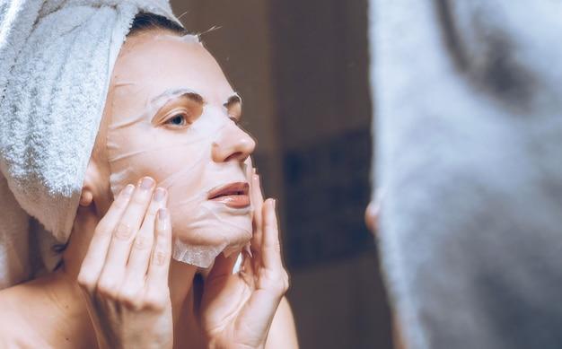 Frau steht in der nähe eines spiegels mit einem handtuch auf dem kopf und setzt eine kosmetische maske auf