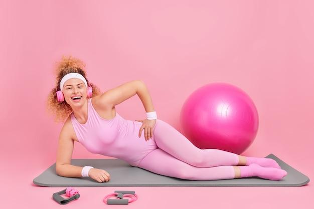 Frau steht in plankenpose auf fitnessmatte in activewear gekleidet hört musik über kopfhörer benutzt sportgeräte