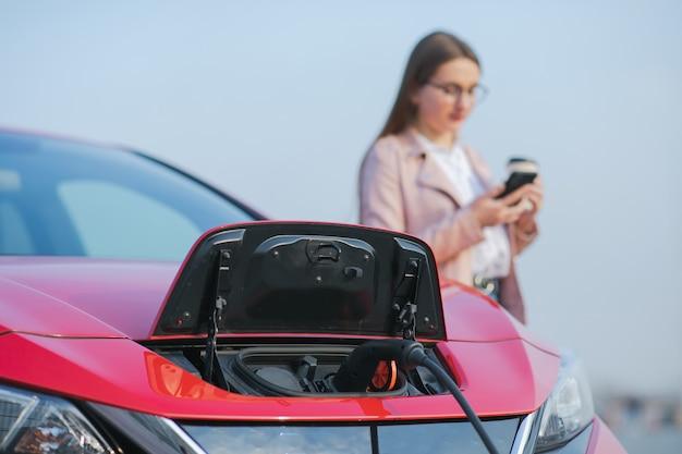 Frau steht mit telefon in der nähe ihres elektroautos und wartet, wenn das fahrzeug aufgeladen wird. aufladen des elektroautos