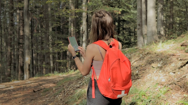 Frau steht mitten im wald und verwendet die navigations-app auf dem smartphone