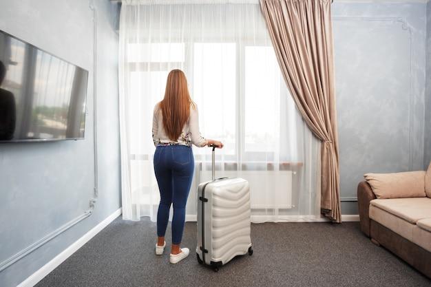 Frau steht nahe dem fenster im hotelzimmer am morgen