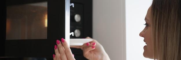 Frau stellt teller mit essen in die mikrowelle