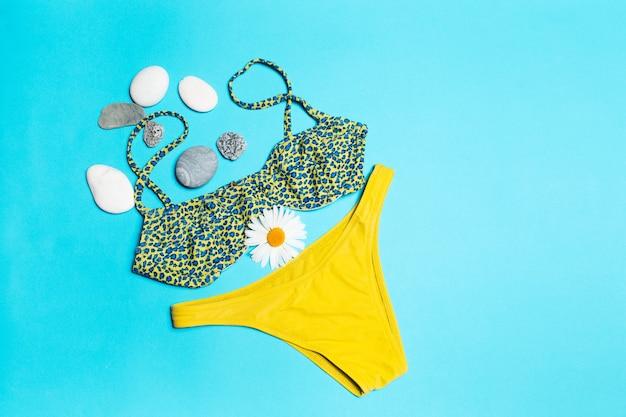 Frau strandzubehör, nahaufnahme draufsicht auf grünen badeanzug mit kamillenblüten verziert?