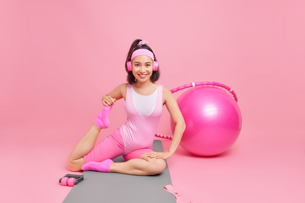 Frau streckt die beine zeigt ihre flexibilität gute laune trägt kopfhörer auf den ohren sportkleidung hört musik beim turnen posiert auf karemat an rosa wand