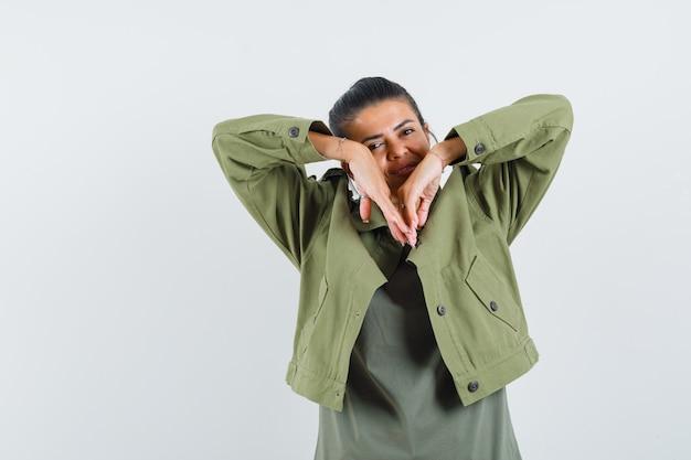 Frau streckt ellbogen in jacke, t-shirt und sieht zart aus