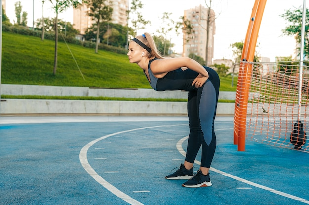 Frau streckt muskeln im fitnessstudio im freien