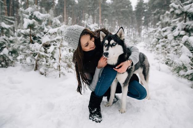 Frau streichelt den heiseren hund am verschneiten kalten wintertag
