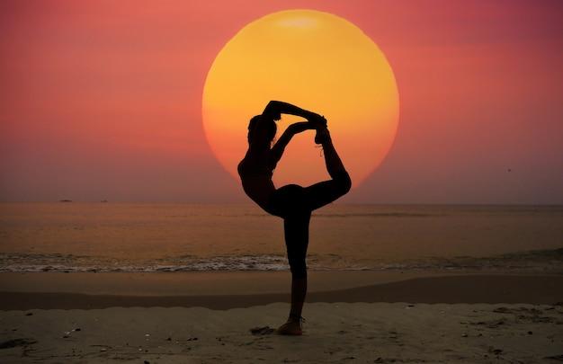 Frau stretching bein von hinten am strand
