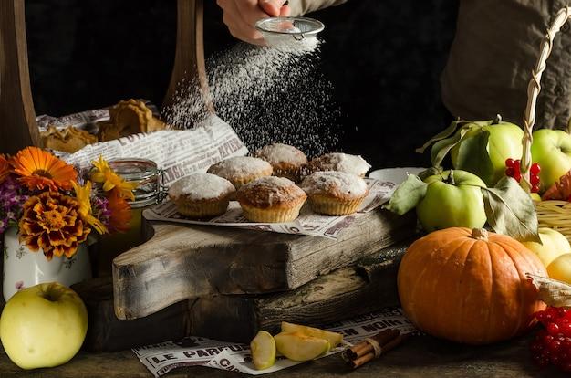Frau streuen puderzucker auf köstliche hausgemachte apfel- und kürbismuffins auf dunkler oberfläche, halloween-herbstbacken