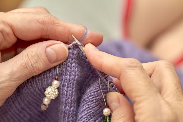 Frau strickt einen blauen warmen pullover