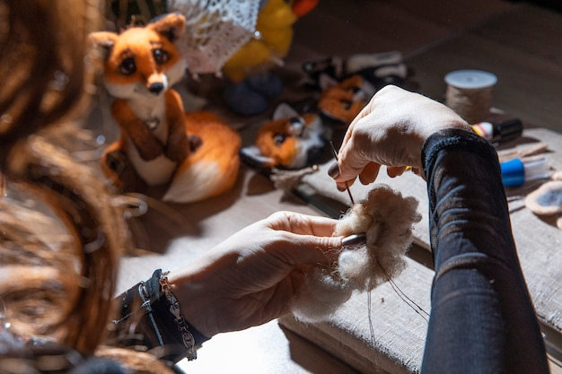 Frau strickt flauschiges spielzeug im atelier