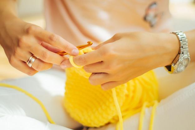 Frau strickt häkeln. das mädchen sitzt und strickt aus strickgarn.