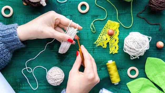 Frau strickt mit haken und weißem garn über dem tisch mit ausrüstung