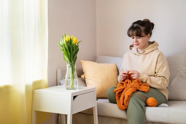 Frau strickt orange pullover allein auf dem sofa zu hause