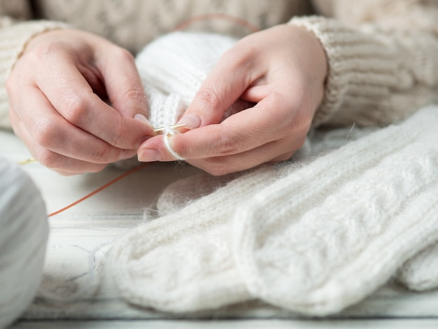 Frau strickt warme kleidungsnahaufnahme des winters