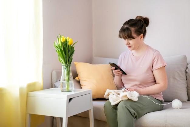 Frau strickt weiße strickwaren auf dem sofa zu hause