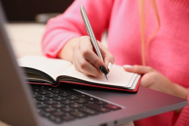 Frau studiert hart, notiert informationen auf notizbuch