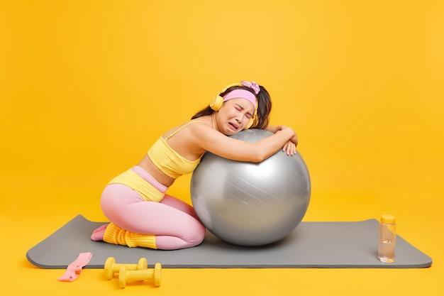 Frau stützt sich auf aufgeblasenen schweizer ball, fühlt sich müde, nachdem sie pilates-übungen in aktivkleidung gemacht hat, hört musik über kopfhörer posiert auf fitnessmatte isoliert auf gelber wand