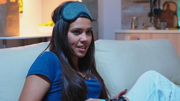 Frau süchtig nach computerspielen, die spät nachts auf der konsole spielen. aufgeregter, entschlossener spieler mit controller-joysticks, tastatur, playstation-spielen und spaß beim gewinnen elektronischer spiele
