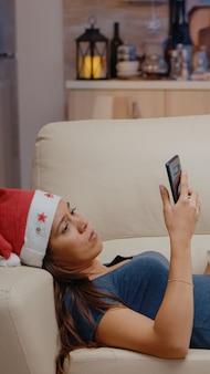 Frau surft mit dem smartphone im internet und sieht fern