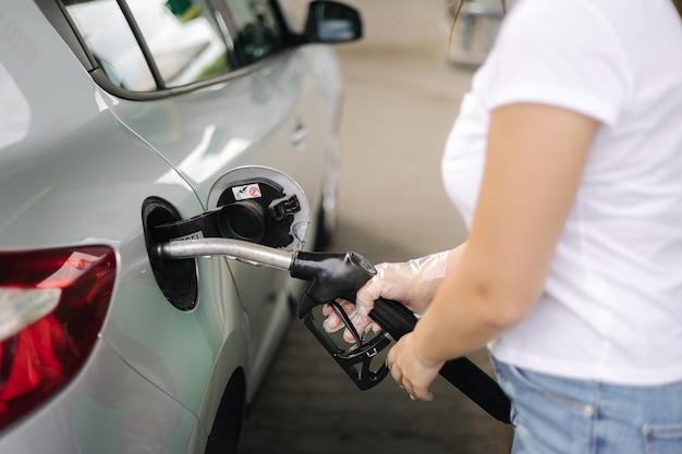 Frau tankt an tankstelle weibliche hand, die benzinkraftstoff in autobenzinpreisen füllt
