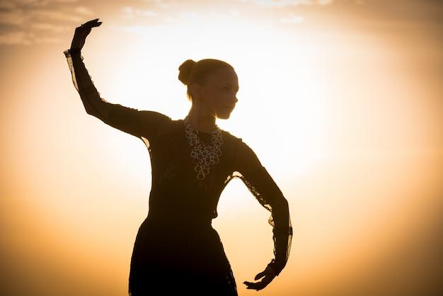 Frau tanzt bei sonnenaufgang