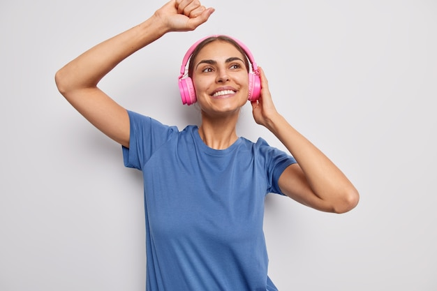 Frau tanzt im rhythmus der musik fängt jedes stück des liedes trägt drahtlose kopfhörer in einem lässigen blauen t-shirt auf weiß gekleidet