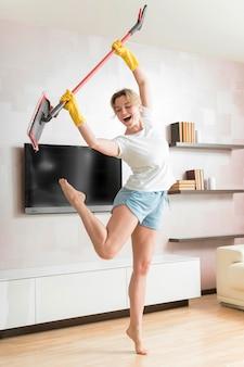 Frau tanzt mit einem mopp