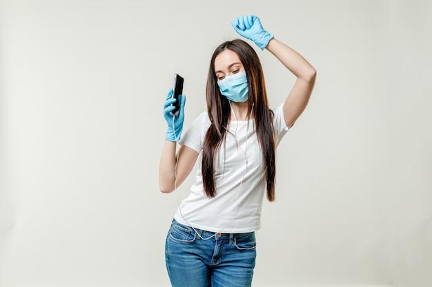 Frau tanzt mit ohrstöpseln, die maske und handschuhe tragen