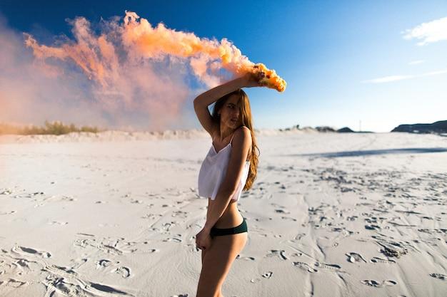 Frau tanzt mit orange rauch am weißen strand unter blauem himmel