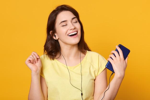 Frau tanzt und hört musik in kopfhörern vom smartphone oder mp3-player
