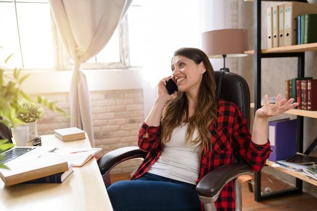 Frau telearbeiterin arbeitet zu hause mit einem laptop und smartphone