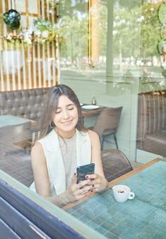 Frau telefoniert mit ihrem handy in einem café
