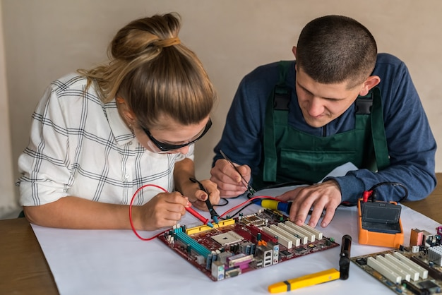 Frau testet motherboard und mann repariert es