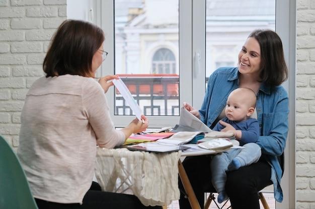 Frau textildesigner und junge mutter mit baby, das stoffe wählt