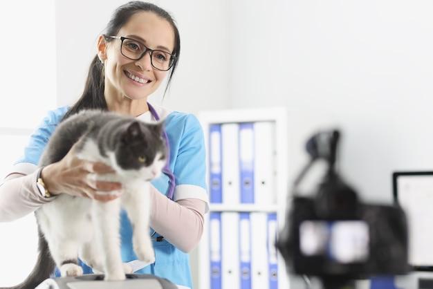 Frau tierarzt hält katze vor der kamera in der klinik