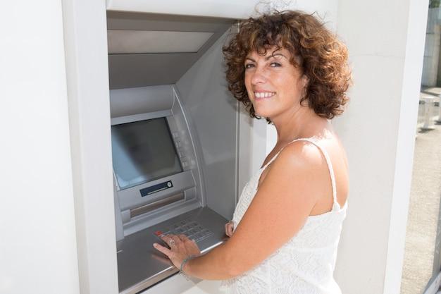 Frau tippt ihren code auf einem banknotenautomaten atm
