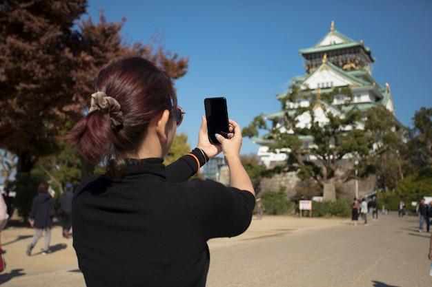 Frau tourist, die ein foto durch smartphone am osaka castle japan macht